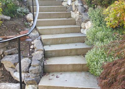 Concrete front staircase surrounded by rock and landscaping