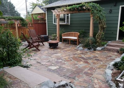 Trellis construction in back yard with rock patio
