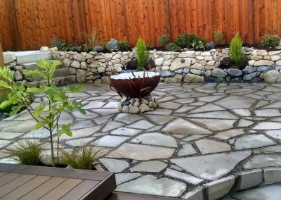 Flagstone patio with fire pit and retaining wall
