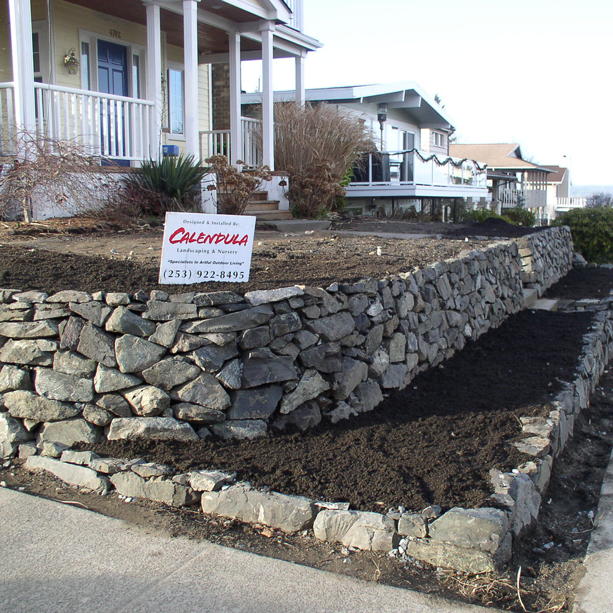 Two tiered stone retaining wall in front yard landscaping