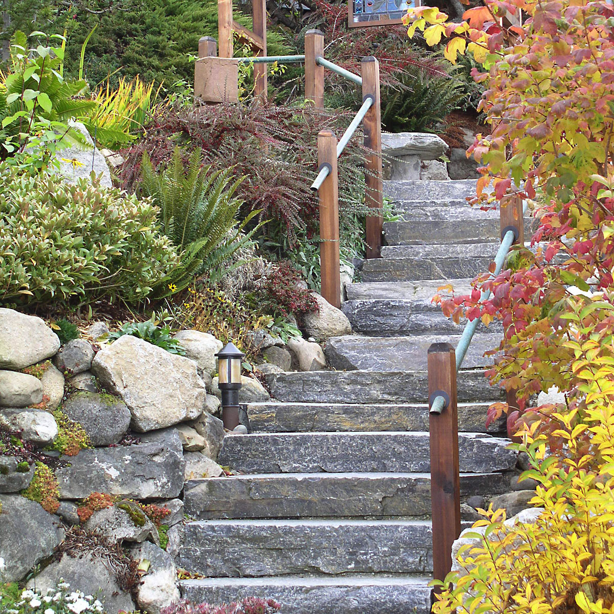 stone staircase with custom wooden rails by Tacoma's best Landscaping company