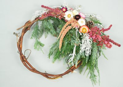 Colorful winter wreath with spruce and flowers