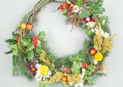 Winter wreath with pine, holly and dried flowers